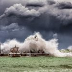 Waves crashing agains a pier with boat